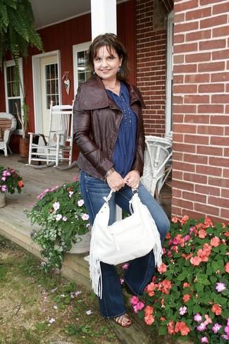 Cómo combinar: chaqueta motera de cuero en marrón oscuro, blusa campesina azul, vaqueros de campana azul marino, botines de cuero con recorte marrónes