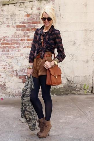 Cómo combinar: chaqueta motera de camuflaje verde, blusa de botones estampada negra, pantalones cortos de ante marrónes, botines con cordones de cuero marrónes