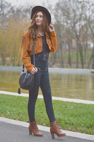 Cómo combinar: chaqueta motera de ante en tabaco, blusa de manga corta de encaje negra, vaqueros pitillo negros, botines con cordones de cuero marrónes