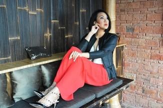Cómo combinar: chaqueta motera de cuero negra, blusa sin mangas blanca, pantalones anchos rojos, zapatos de tacón de cuero con tachuelas negros