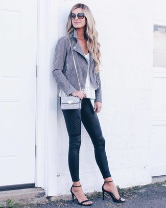 Cómo combinar: chaqueta motera de ante gris, blusa sin mangas blanca, pantalones pitillo de cuero acolchados negros, sandalias de tacón de ante negras