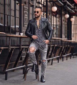 Cómo combinar: chaqueta motera de cuero negra, camisa de manga larga estampada en negro y blanco, vaqueros desgastados grises, botines chelsea de cuero negros