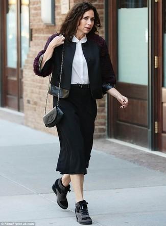 Cómo combinar: chaqueta motera de lana negra, camisa de vestir de seda blanca, falda midi negra, zapatillas con cuña de ante negras
