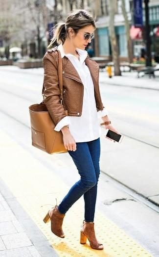 Cómo combinar: chaqueta motera de cuero marrón, camisa de vestir blanca, vaqueros pitillo azul marino, botines de ante con recorte marrónes