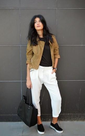 Cómo combinar: chaqueta motera de ante marrón, camiseta con cuello circular negra, pantalones pitillo de seda blancos, zapatillas slip-on de cuero negras