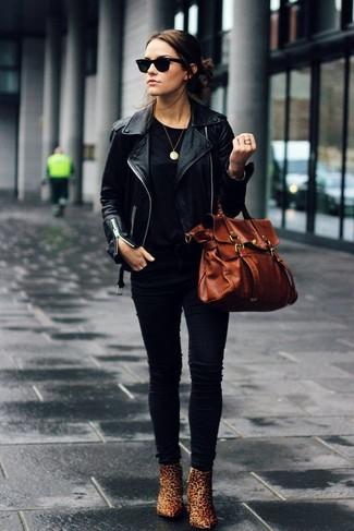 Cómo combinar: chaqueta motera de cuero negra, camiseta con cuello circular negra, vaqueros pitillo negros, botines de cuero de leopardo marrón claro
