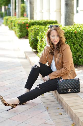 Cómo combinar: chaqueta motera de cuero marrón claro, camiseta con cuello circular blanca, vaqueros pitillo negros, zapatos de tacón de ante de leopardo marrón claro
