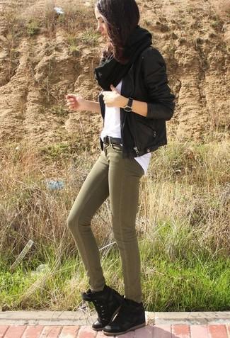 Cómo combinar: chaqueta motera de cuero negra, camiseta con cuello circular blanca, vaqueros pitillo verde oliva, zapatillas con cuña de ante negras