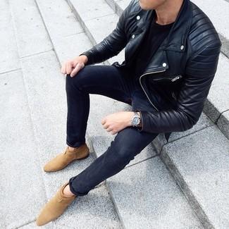 Cómo combinar: chaqueta motera de cuero negra, camiseta con cuello circular negra, vaqueros pitillo en gris oscuro, botines chelsea de ante marrón claro