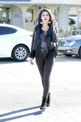Cómo combinar: chaqueta motera de cuero сon flecos negra, camiseta con cuello en v estampada negra, leggings negros, botines con cordones de ante negros