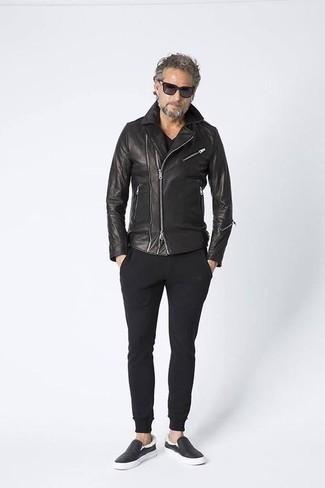 Cómo combinar una camiseta con cuello en v negra: Ponte una camiseta con cuello en v negra y un pantalón de chándal negro para un look agradable de fin de semana. ¿Te sientes valiente? Complementa tu atuendo con zapatillas slip-on de cuero negras.