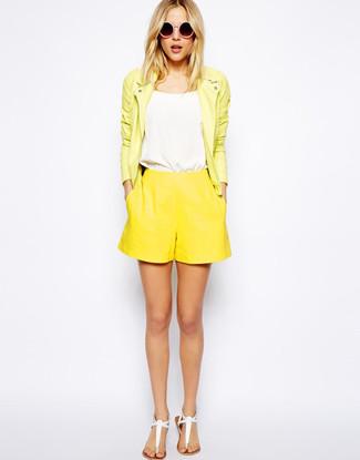 Cómo combinar: chaqueta motera de cuero amarilla, camiseta sin manga blanca, pantalones cortos amarillos, sandalias de dedo de cuero blancas
