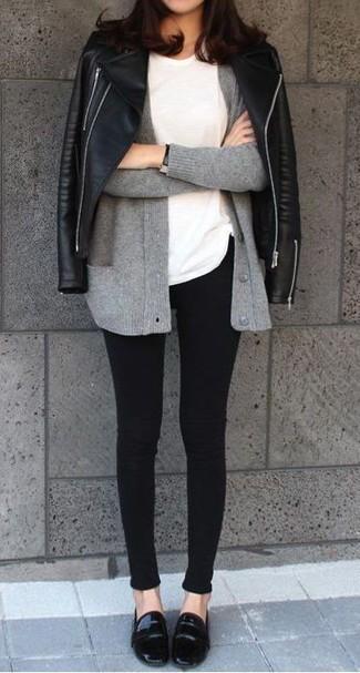 Cómo combinar: chaqueta motera de cuero negra, cárdigan gris, camiseta con cuello circular blanca, vaqueros pitillo negros