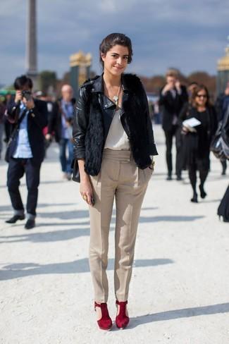 Cómo combinar: chaqueta motera de cuero negra, chaleco de pelo negro, camiseta sin manga de seda blanca, pantalón de pinzas en beige