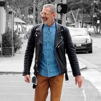 Cómo combinar: chaqueta motera de cuero negra, camisa de manga larga de cambray azul, pantalón chino en tabaco