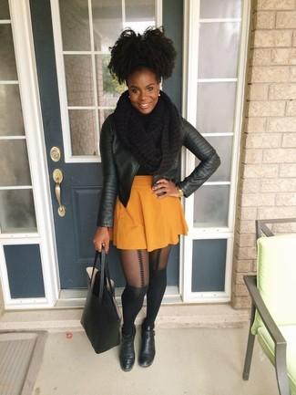 Cómo combinar: chaqueta motera de cuero negra, falda skater naranja, botines de cuero negros, bolsa tote de cuero negra