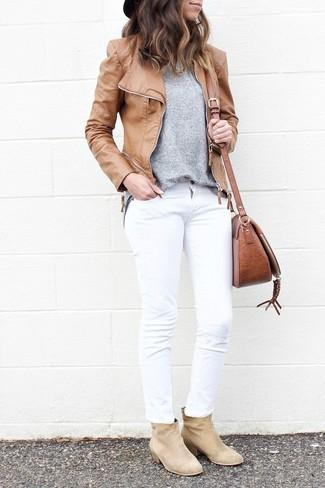 Cómo combinar: chaqueta motera de cuero marrón claro, jersey con cuello circular gris, vaqueros blancos, botines de ante en beige