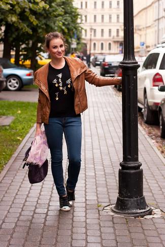 Cómo combinar: chaqueta motera de cuero en tabaco, jersey con cuello circular con adornos negro, vaqueros pitillo azul marino, tenis negros