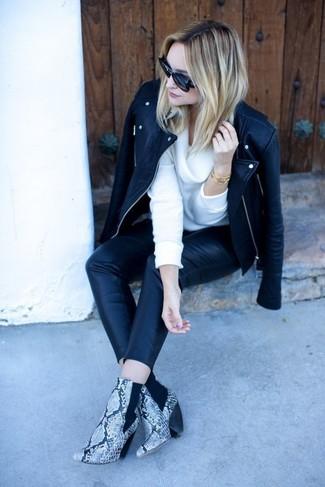 Cómo combinar: chaqueta motera de cuero negra, jersey con cuello vuelto holgado blanco, pantalones pitillo de cuero negros, botines de cuero con print de serpiente grises