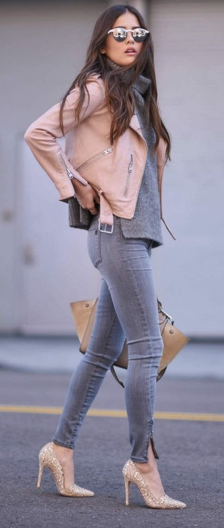 Cómo combinar: chaqueta motera de cuero rosada, jersey con cuello vuelto holgado gris, vaqueros pitillo grises, zapatos de tacón de lentejuelas dorados
