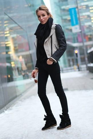 Cómo combinar: chaqueta motera de cuero en negro y blanco, jersey de cuello alto negro, vaqueros pitillo negros, zapatillas con cuña de ante negras