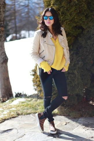 Cómo combinar: chaqueta motera de cuero en beige, jersey oversized de punto amarillo, vaqueros pitillo desgastados negros, botines chelsea de ante de leopardo marrónes