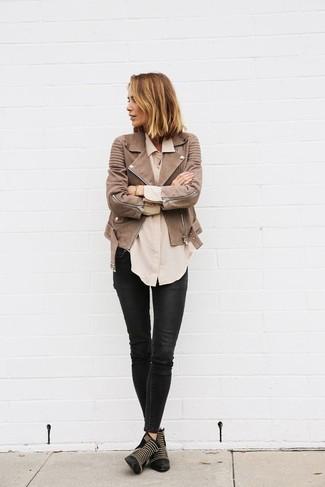 Cómo combinar: chaqueta motera de cuero marrón, camisa de vestir en beige, vaqueros pitillo de cuero negros, botines de cuero con tachuelas negros