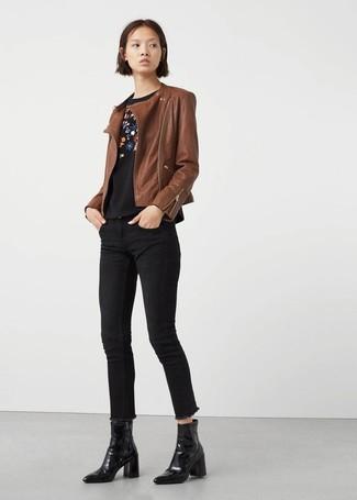 Cómo combinar: chaqueta motera de cuero marrón, jersey con cuello circular con print de flores negro, vaqueros pitillo negros, botines de cuero negros
