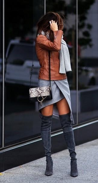Cómo combinar: chaqueta motera de cuero en tabaco, minifalda con recorte gris, botas sobre la rodilla de ante en gris oscuro, bolso bandolera de cuero con print de serpiente gris