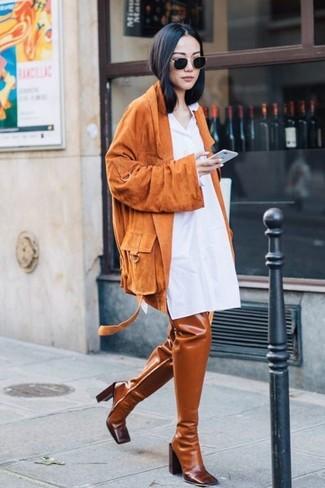 Cómo combinar: chaqueta motera de ante naranja, vestido camisa blanca, botas sobre la rodilla de cuero en tabaco, gafas de sol negras