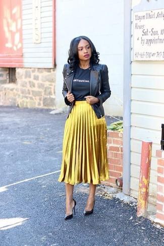 Cómo combinar: chaqueta motera de cuero negra, camiseta con cuello circular estampada en negro y blanco, falda midi plisada dorada, zapatos de tacón de cuero negros
