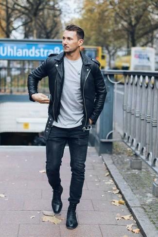 Cómo combinar: chaqueta motera de cuero negra, camiseta con cuello circular gris, vaqueros pitillo negros, botas formales de cuero negras