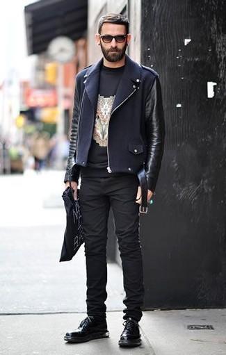 Cómo combinar: chaqueta motera de cuero negra, camiseta con cuello circular estampada negra, vaqueros pitillo negros, zapatos derby de cuero negros