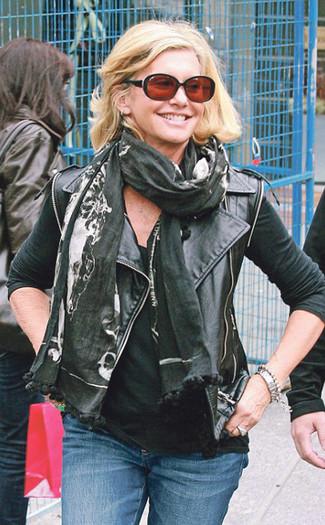 Cómo combinar: chaqueta motera de cuero negra, camiseta sin manga negra, vaqueros azules, bufanda estampada negra
