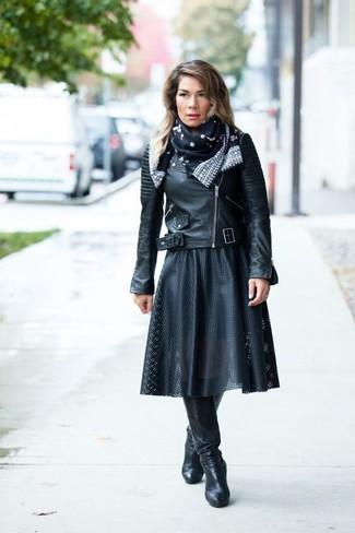 Cómo combinar: chaqueta motera de cuero negra, falda midi de cuero plisada negra, botas de caña alta de cuero negras, bufanda de seda estampada en negro y blanco