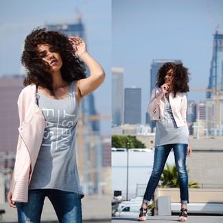 Cómo combinar: chaqueta motera de cuero rosada, camiseta sin manga estampada gris, vaqueros pitillo desgastados azules, sandalias de tacón de cuero negras