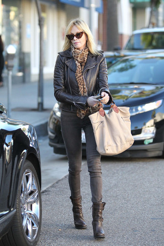 Cómo combinar: chaqueta motera de cuero negra, vaqueros grises, botines de cuero negros, bolsa tote de lona marrón claro