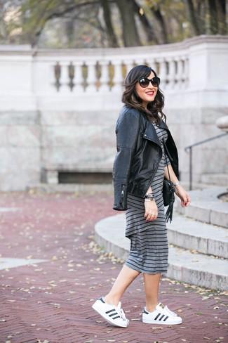 Cómo combinar: chaqueta motera de cuero acolchada negra, vestido ajustado de rayas horizontales gris, tenis de cuero en blanco y negro, bolso bandolera de cuero negro