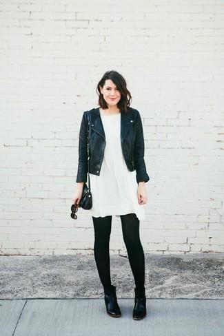 Cómo combinar: chaqueta motera de cuero negra, vestido amplio blanco, botines chelsea de cuero negros, bolso bandolera de cuero negro