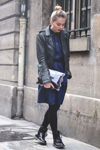 Cómo combinar: chaqueta motera de cuero negra, vestido camisa vaquera azul marino, botas planas con cordones de cuero negras, cartera sobre de cuero plateada