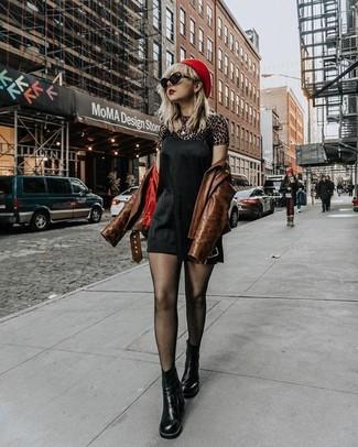 Cómo combinar: chaqueta motera de cuero marrón, vestido camisola de seda negro, camiseta con cuello circular de leopardo marrón, botines chelsea de cuero negros