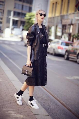 Cómo combinar: chaqueta motera de cuero negra, vestido midi de encaje negro, tenis de cuero en blanco y negro, bolso de hombre de cuero negro