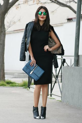 Cómo combinar: chaqueta motera de cuero negra, vestido tubo negro, botines de cuero con adornos negros, cartera sobre de cuero azul marino
