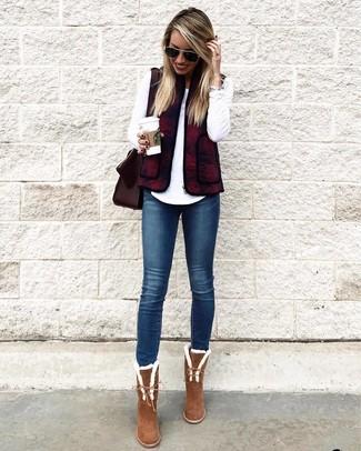 Cómo combinar: chaqueta sin mangas burdeos, camiseta de manga larga blanca, vaqueros pitillo azul marino, botines de ante marrónes