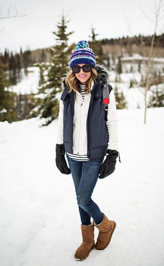 Cómo combinar: chaqueta sin mangas en gris oscuro, jersey con cremallera blanco, jersey de cuello alto de rayas horizontales en blanco y negro, vaqueros pitillo azul marino