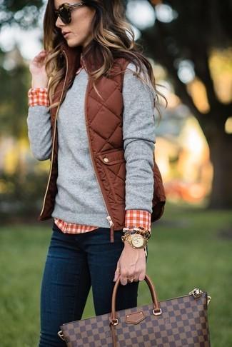 Cómo combinar: chaqueta sin mangas acolchada marrón, jersey con cuello circular gris, camisa de vestir de cuadro vichy en rojo y blanco, vaqueros pitillo azul marino
