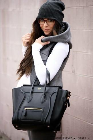Elige por la comodidad con una chaqueta sin mangas gris y unos leggings gris oscuro.