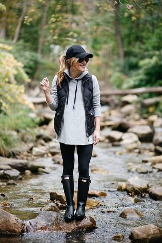 Cómo combinar: chaqueta sin mangas acolchada negra, sudadera con capucha gris, leggings negros, botas de lluvia negras