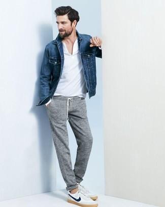 Cómo combinar: chaqueta vaquera azul, camiseta con cuello en v blanca, pantalón de chándal gris, tenis blancos