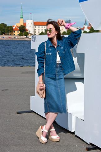 Cómo combinar: chaqueta vaquera azul, blusa sin mangas de gasa blanca, falda midi vaquera azul, sandalias con cuña de cuero blancas